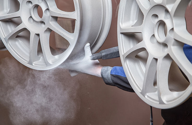 powder coatings being applied to a wheel